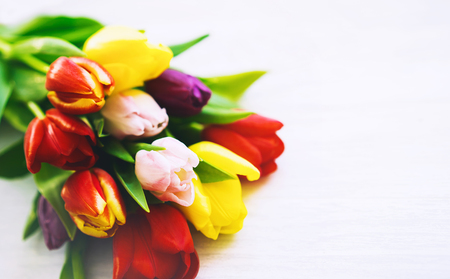 Bouquet of spring flowers. Beautiful tulips on wooden white background with copy space. Flat lay, top view. Stock Photo