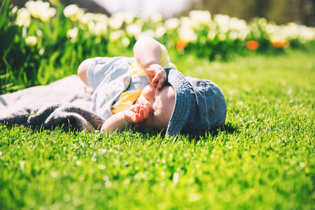 Cute squinting in the sun baby girl lying in green grass of tulip field. Child playing outdoors in spring park. Image of Mothers Day, Easter. Family on nature in Arboretum, Slovenia, Europe. Stock Photo
