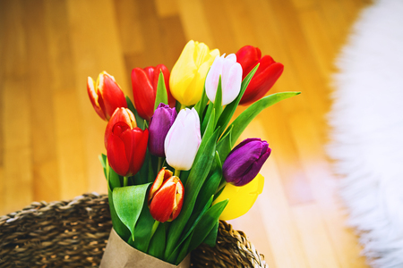 Beautiful tulips on background of home interior. Spring flowers bouquet in wicker straw basket.