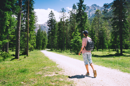 Hiker woman outdoors on nature. Travel at Dolomites, Italy, Europe. Summer holiday in South Tyrol. Girl tourist in forest with mountains on background.