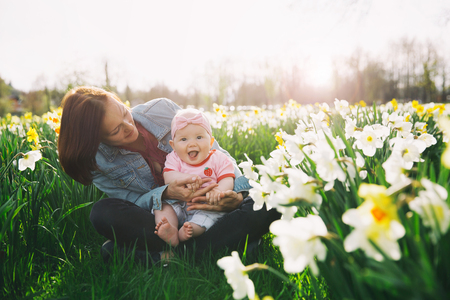 Beautiful loving mother and baby girl in daffodils flowers field at springtime. Young woman with her cute little daughter playing outdoors. Family on nature in Arboretum, Slovenia. Banque d'images - 119737513
