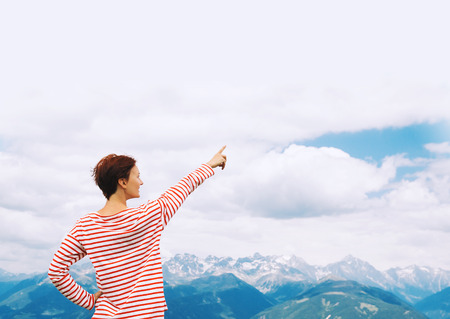 Hiker woman pointing out finger in sky with mountains on background. Travel at Dolomites, Italy, Europe. Summer holiday in South Tyrol. View of Bruneck and Pustertal from the summit of Kronplatz Stok Fotoğraf