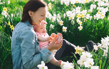Beautiful loving mother and baby girl in daffodils flowers field at springtime. Young woman with her cute little daughter playing outdoors. Family on nature in Arboretum, Slovenia. Banque d'images - 119737519