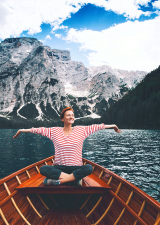Tourist woman in traditional wooden rowing boat on italian alpine Braies Lake. Girl enjoying stunning view of Lago di Braies in Dolomites, South Tyrol, Italy, Europe. Beauty of nature background. Stok Fotoğraf