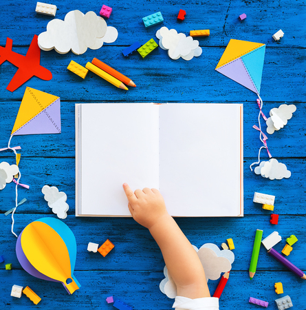 Ð¡olourful toy bricks, paper crafts and blank book with child hands on blue wood board. School or preschool creative background. Concept of DIY, construction, playing education or learning languages