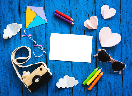 Creative childrens background, top view. Paper crafts, colored pencils, photo camera with blank card for text on blue table. DIY, study languages, kids creativity class or travel concept