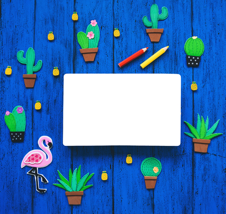 Creative colourful background with trendy hand drawn and cut elements - cactuses, pineapples, pink flamingo and blank book for text. Tropical exotic hand made set on blue texture table, top view.
