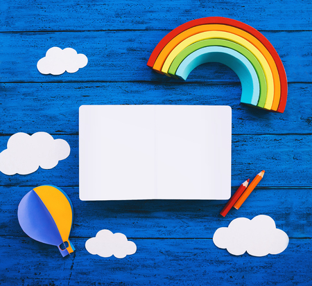 Creative childrens waldorf montessori school or travel concept. Paper crafts, colored pencils, wood rainbow and blank book for text on blue table. Kids art class, kindergarten, preschool background
