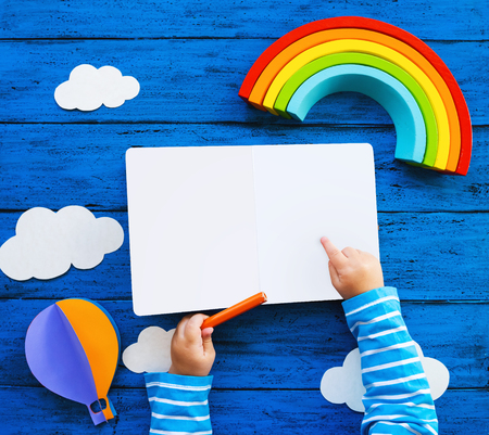 Creative childrens waldorf or montessori school concept. Paper crafts, colored pencils, wood rainbow and blank book with child hands on blue table. Kids art class, kindergarten, preschool background
