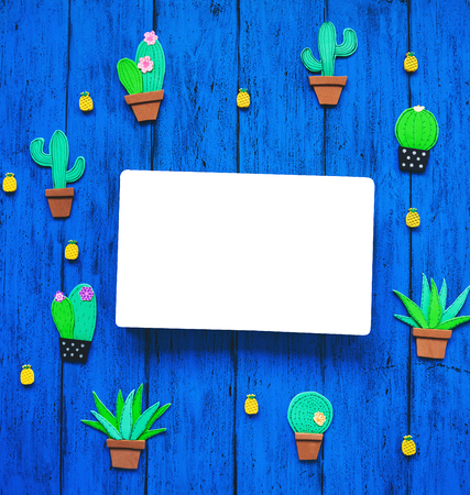 Creative colourful background with trendy hand drawn and cut elements - cactuses and pineapples, with blank book for text. Tropical exotic hand made set on blue texture table, top view.