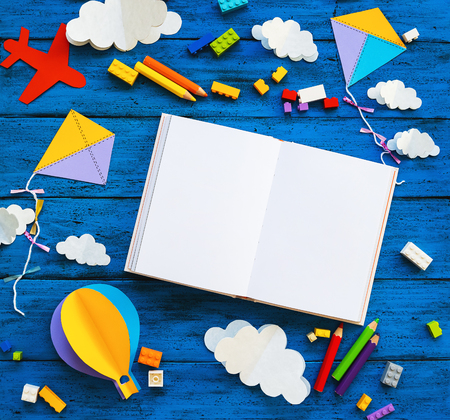 Ð¡olourful toy bricks, paper crafts and blank book on blue wood board. School or preschool creative background. Concept of DIY, construction, adventure, playing child education or kids learn languages