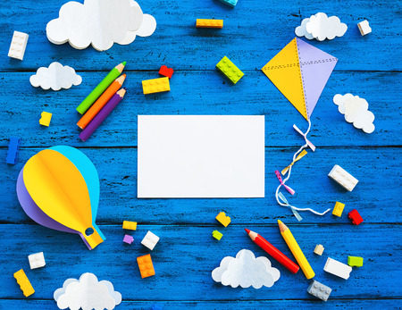 Ð¡olourful toy bricks, paper crafts and blank card on blue wood board. School or preschool creative background. Concept of DIY, construction, adventure, playing child education or kids learn languages Stock Photo