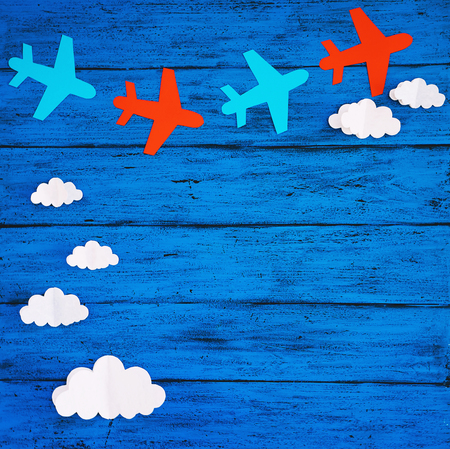 Paper handmade crafts: clouds and airplanes on the blue wood background. Top view, copy space.