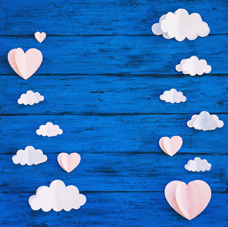 Paper handmade crafts: clouds and hearts on the blue wood background. Top view, copy space. Stockfoto