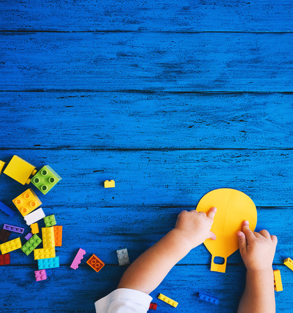 Creative colourful kid's background, top view. Paper crafts, toy bricks, playing or making child hands on blue wood table. DIY, learn languages, art creativity class, construction or travel themes