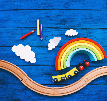 Wooden toy train, railway for preschool child, wood rainbow, colored pencils on blue table. Daycare, kindergarten or montessori school background. Kids dream, Learn and Play concept 免版税图像