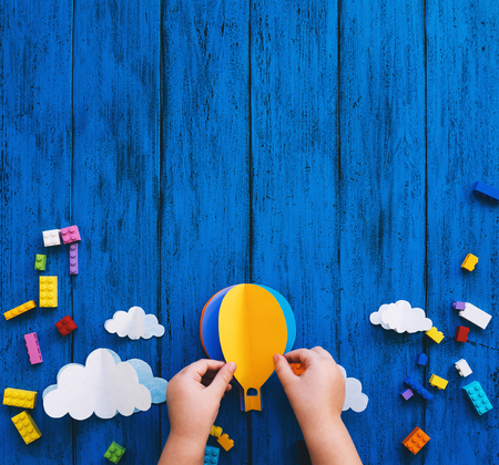 Creative colourful kids background, top view. Paper crafts, toy bricks, playing or making child hands on blue wood table. DIY, learn languages, art creativity class, construction or travel themes Stock Photo