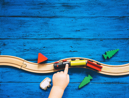 Preschool or kindergarten background with toys. Childs hands playing with wooden toy train set and railway on blue table. Kids dream, travel concept. Top view, flat lay, copy space.