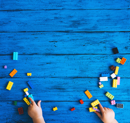 Building kids blocks on table, top view. Child hands playing or constructing colourful toy bricks on blue wood background