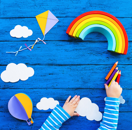 Creative childrens waldorf or montessori school concept. Paper crafts, colored pencils, wood rainbow with child hands on blue table. Kids art class, kindergarten, preschool background with copy space Stock Photo