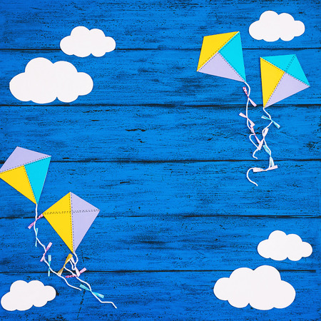 Paper handmade crafts: clouds and kites on the blue wood background. Top view, copy space. Stock Photo