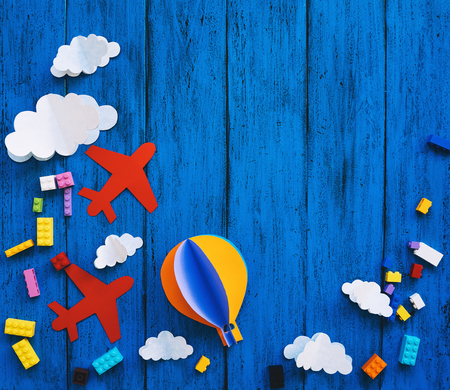 Creatieve kinderachtergrond met kopieerruimte voor tekst, bovenaanzicht. Papierambachten, kleurrijke speelgoedbakstenen op blauwe houten tafel. Doe-het-zelf, talen studeren, creativiteitslessen voor kinderen, avontuur of reisthema's