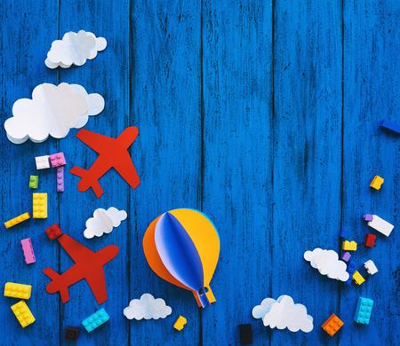 Fondo infantil creativo con espacio para copiar texto, vista superior. Artesanías de papel, ladrillos de juguete de colores en la mesa de madera azul. Bricolaje, estudio de idiomas, clases de creatividad para niños, temas de aventura o viajes