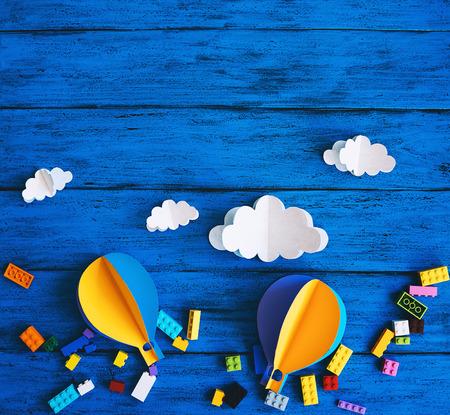 Kreativer Kinderhintergrund mit Kopienraum für Text, Draufsicht. Papierhandwerk, bunte Spielzeugziegel auf blauem Holztisch. DIY, Sprachen lernen, Kreativitätskurs für Kinder, Abenteuer- oder Reisethemen Standard-Bild