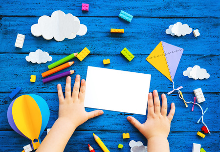 Ð¡olourful toy bricks, paper crafts and blank card with child hands on blue wood board. School or preschool creative background. Concept of DIY, construction, playing education or learning languages Zdjęcie Seryjne