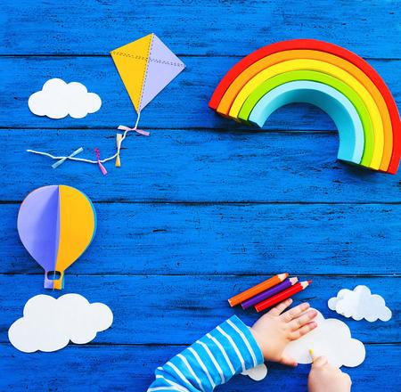 Concepto de escuela waldorf o montessori para niños creativos. Artesanías de papel, lápices de colores, arco iris de madera con manos de niño sobre mesa azul. Clase de arte para niños, jardín de infantes, fondo preescolar con espacio de copia