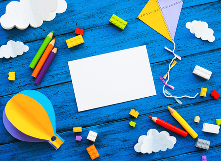 Ð¡olourful toy bricks, paper crafts and blank card on blue wood board. School or preschool creative background. Concept of DIY, construction, adventure, playing child education or kids learn languages Zdjęcie Seryjne