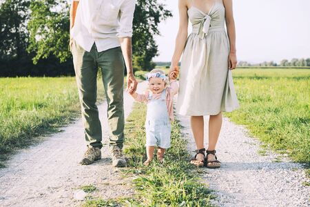 Family on nature at summer. Mother and father with one year old baby girl outdoors. Woman and man with child in countryside. Photo of natural parenthood, slow fashion, conscious life, eco lifestyle. Stock Photo