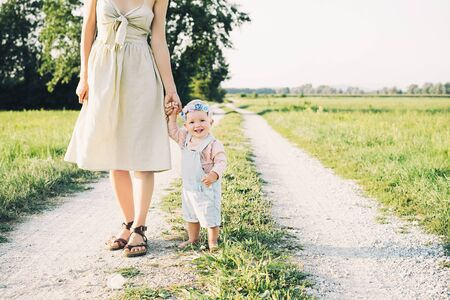 Mother and baby outdoors. Family on nature. Loving woman with child in countryside. Photo of natural parenthood, maternity leave. Theme of zero waste, slow fashion and conscious life, eco lifestyle Stock Photo - 125823135