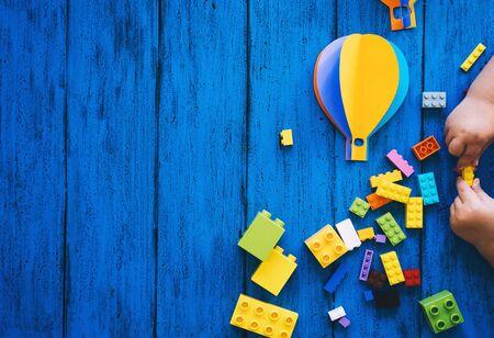 Creatieve kleurrijke kid's achtergrond, bovenaanzicht. Papierambachten, speelgoedstenen, spelen of kinderhanden maken op blauwe houten tafel. DIY, talen leren, kunstcreativiteitsles, constructie- of reisthema's