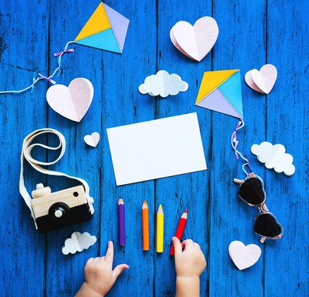 Creative childrens background, top view. Paper crafts, colored pencils, photo camera and blank card with child hands on blue table. DIY, study languages, kids creativity class or travel concept