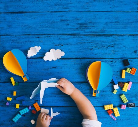 Creative colourful kids background, top view. Paper crafts, toy bricks, playing or making child hands on blue wood table. DIY, learn languages, art creativity class, construction or travel themes Zdjęcie Seryjne