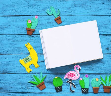 Creative colourful background with trendy hand drawn and cut elements - llama or lama, cactuses, pink flamingo and blank book for text. Tropical exotic hand made set on blue texture table, top view.