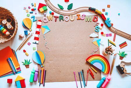 Sfondo per scuola materna o scuola materna o lezioni d'arte. Giocattoli educativi per bambini e materiale scolastico per disegnare e realizzare oggetti fai-da-te. Vista dall'alto piatta. Cornice per bambini d'arte con carta vuota, mock up per il testo