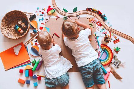 Kinder zeichnen und basteln. Kinder mit Lernspielzeug und Schulmaterial für Kreativität. Hintergrund für Vorschule und Kindergarten oder Kunstunterricht. Jungen und Mädchen spielen zu Hause oder in der Kita