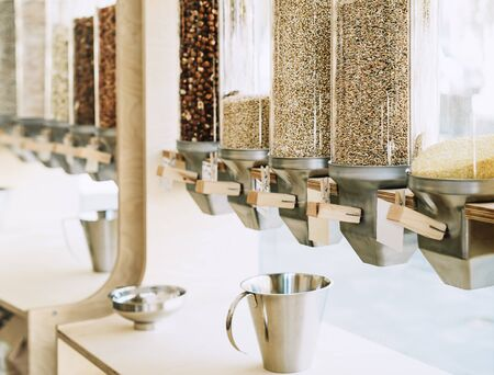 Eco-friendly zero waste shop. Dispensers for cereals, nuts and grains in sustainable plastic free grocery store. Bio organic food. Shopping at small local businesses. New trend alternative buying
