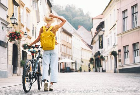 Travel Slovenia, Europe. Young girl with backpack and urban bicycle in old street in historical center of Ljubljana. Traveler woman explores sights of european city. Local living in Ljubljana.