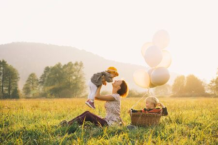 Young mother with children with balloons in sunlight at sunset on nature outdoors. Parents and kids in meadow in autumn. Photo of leisure, dreams, holidays, family values, sustainable lifestyle.