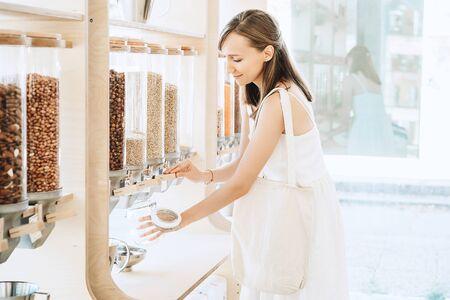 Femme avec un sac en coton et un bocal en verre achetant dans un magasin zéro déchet. Distributeurs de céréales, céréales, noix dans une épicerie sans plastique. Achats durables dans les petites entreprises locales. Nourriture biologique Eco Bio