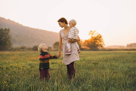 Young mother with children in sunlight at sunset on nature outdoors. Parents and kids in meadow in early autumn. Photo of natural parenting, dreams, family values, sustainable lifestyle. 写真素材