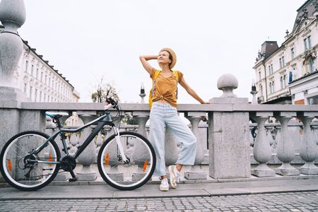 Travel Slovenia, Europe. Young girl with urban bicycle on Triple Bridge in center old town of Ljubljana. Traveler woman explores sights on background of city architecture. Local living in Ljubljana