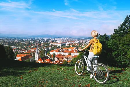 Travel Slovenia Europe. Woman tourist looking at panoramic view of cityscape with red roofs of Ljubljana from City Castle. Young girl with bicycle on top of green hill explores sights and local living 版權商用圖片