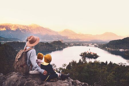 Journey Slovenia with kids. Family travel Europe. Hiker woman with children on Bled Lake among nature and Alps mountains. Traveling mother with backpack with her kids at autumn or winter vacation