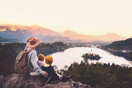 Reisen Sie mit Kindern durch Slowenien. Familienreisen Europa. Wandererfrau mit Kindern am Bleder See zwischen Natur und Alpenbergen. Reisemutter mit Rucksack mit ihren Kindern im Herbst- oder Winterurlaub