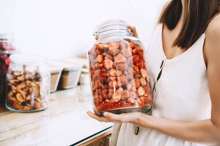 Femme avec des bocaux en verre achetant des baies et des fruits séchés dans un magasin zéro déchet. Achats durables dans une épicerie sans plastique. Mode de vie minimaliste d'une jeune fille végétalienne avec un sac en coton réutilisable blanc