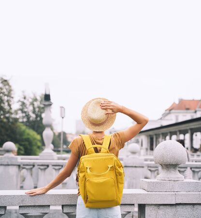 Travel Slovenia, Europe. Young girl with backpack on Triple Bridge in heart of Ljubljana Old Town. Back view of woman tourist on the background of city architecture. Local living in Ljubljana
